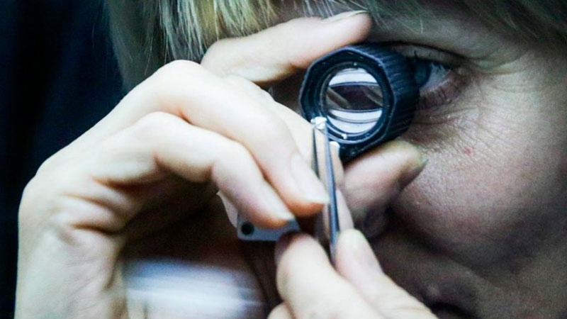 Рассматривает алмаз фото